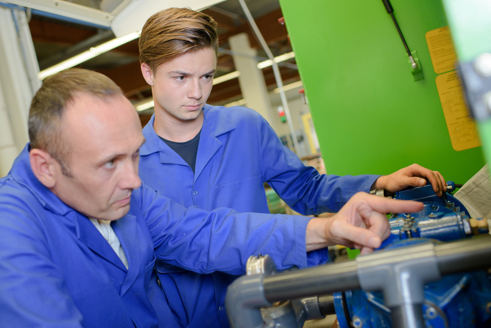 Engineers examining machine and engineer
